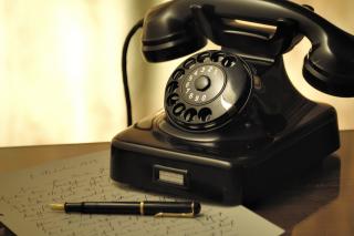 Black-rotary-telephone-beside-ball-pen-on-white-printed-47319